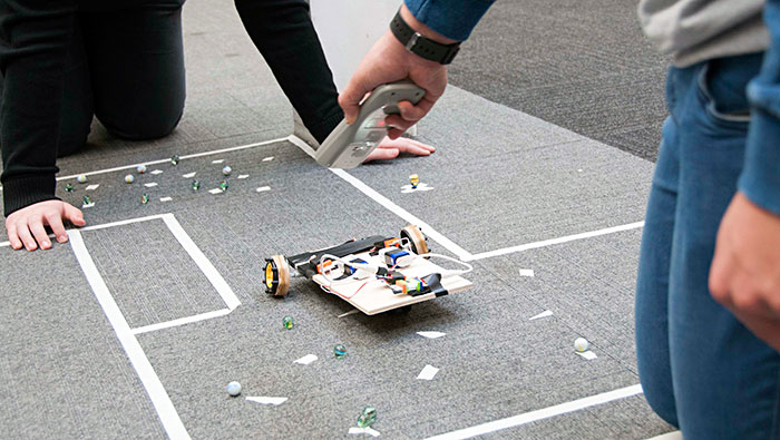 Remote controlled vehicle on obstacle course of marbles